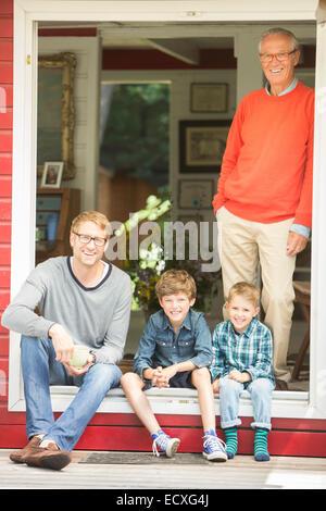 Brüder, die lächelnd mit Vater und Großvater - Stockfoto