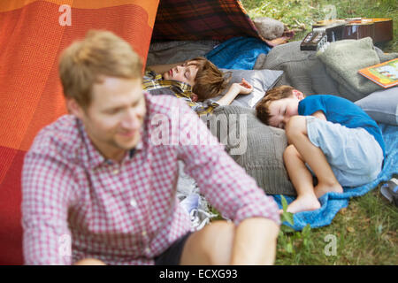 Vater mit Söhnen am camping Zelt schlafen sitzend - Stockfoto