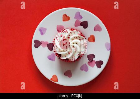 Tesco Frohe Weihnachten Red Velvet Cupcake mit einer versteckten Sauce Center auf Herz Platte auf rotem Hintergrund - Stockfoto