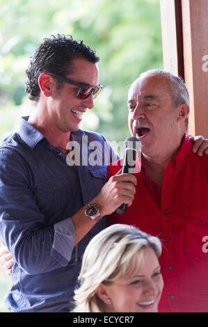 Großvater und Enkel sprechen ins Mikrofon auf Familientreffen - Stockfoto