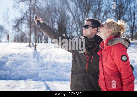 Kaukasische paar unter Handy Selfie im winter - Stockfoto