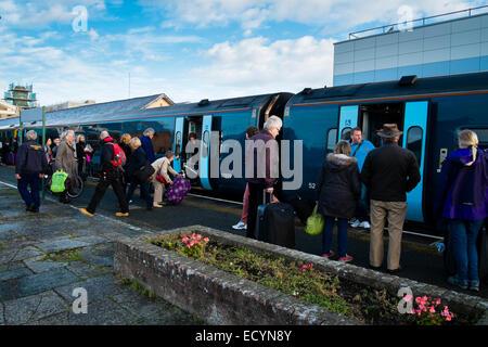 Reisenden Passagiere auf der Plattform ein Arriva Trains Wales einsteigen Zug am Bahnhof von Aberystwyth, Wales - Stockfoto