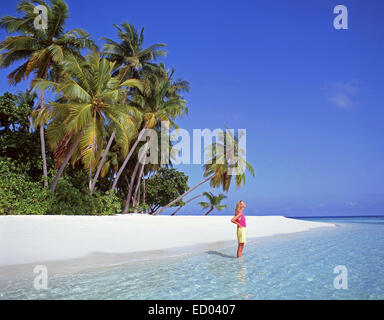 Junge Frau am tropischen Strand, Republik Malediven, Kuda Bandos Island, Kaafu Atoll - Stockfoto