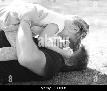 Vater liegt auf dem Gras und spielt mit seiner Tochter