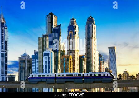Blick auf moderne Gebäude mit u-Bahn bei Sonnenuntergang in der Dubai Marina, Dubai - Stockfoto