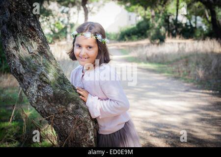 """Porträt eines Mädchens (6-7) in """"Girlande"""" Baumstamm gelehnt - Stockfoto"""