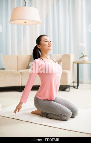 Junge Frau praktizieren Yoga im Wohnzimmer - Stockfoto