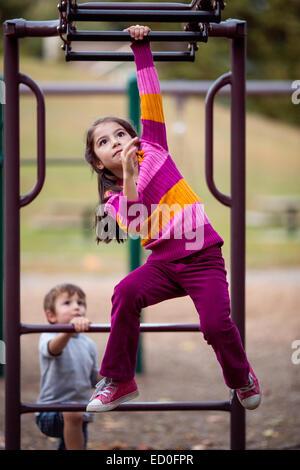 Mädchen und Junge spielen auf Klettergerüst auf einem Spielplatz Stockfoto