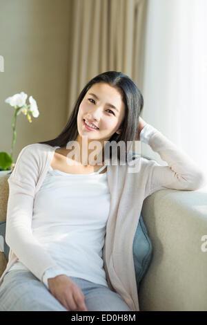 Glückliche junge Frau sitzt auf dem sofa - Stockfoto