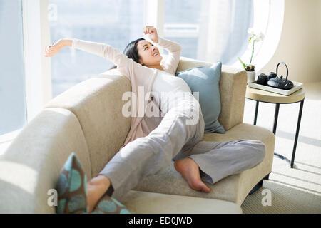 Junge Frau, die Dehnung auf sofa - Stockfoto