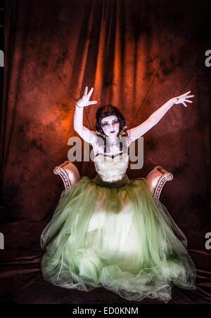 Fantasy-Makeover-Fotografie: eine junge Frau-Mädchen-Modell gebildet um zu schauen wie White-faced bemalte Puppe Porzellan und posiert wie eine Puppe in einem Fotostudio tragen eine große grüne Kleid Kleid Ballkleid