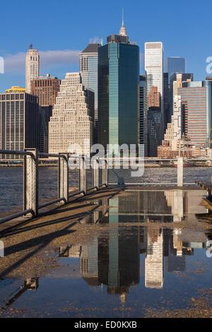 Lower Manhattan Skyline von der Brooklyn Bridge Park betrachtet spiegelt sich in einer Pfütze über den East River - Stockfoto
