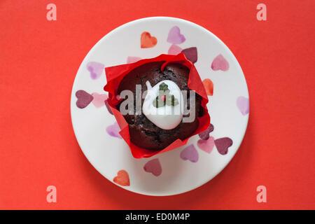 Tesco Frohe Weihnachten Christmas Pudding Muffin auf Herz Teller isoliert auf rotem Grund - Stockfoto