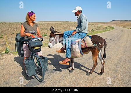 Weibliche Radfahrer auf Tourenrad Fragen Anfahrt ein türkischer Mann auf Esel in der Westtürkei - Stockfoto