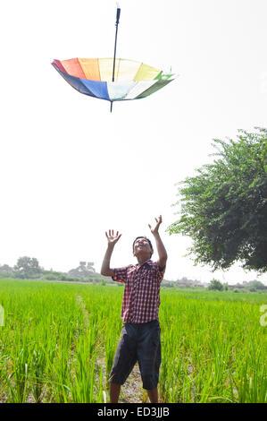 Genießen Sie 1 ländliche Kind junge Bauernhof fangen Regenschirm Regensaison - Stockfoto
