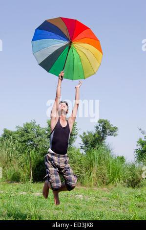 1 junge ländlichen Bauernhof Jumping hält Regenschirm Regensaison genießen - Stockfoto