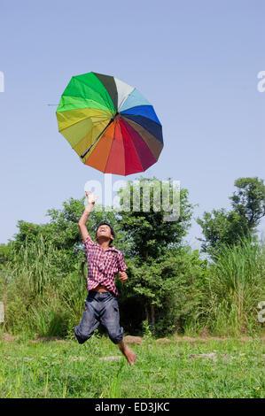 1 ländliche Kind junge Bauernhof Jumping hält Regenschirm Regensaison genießen - Stockfoto
