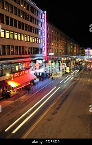 Stockholm, Schweden - 7. Dezember 2013: Nachtverkehr auf Kungsgatan im Zentrum von Stockholm. Autos, Fußgänger, - Stockfoto
