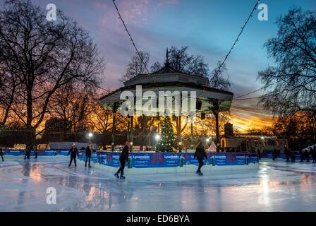 Skater auf Eisbahn rund um den Musikpavillon im Hyde Park im Winter-Wunderland - Stockfoto