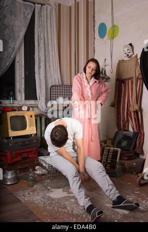 Böse Frau in rosa Gewand zeigt ihr sitzen stillen Gesellschafters an den unordentlichen Zimmer. - Stockfoto