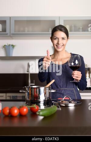 Lächelnde Hausfrau geben einen Daumen nach oben Geste, wie sie genießt ein Glas Rotwein im stehen am Herd kochen - Stockfoto