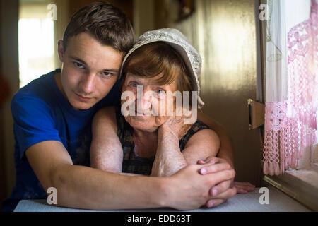 Oma mit ihrem Enkel im Haus posiert für die Kamera. - Stockfoto