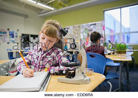 Elementare Schüler schreiben neben Mikroskop im Labor - Stockfoto