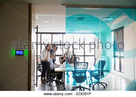 Business-Leute drängten sich um Konferenztisch - Stockfoto