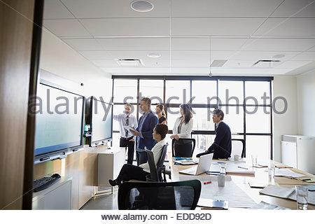 Business-Leute treffen um Monitor im Konferenzraum - Stockfoto