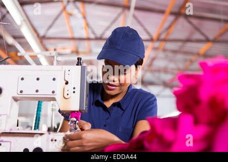 hübsche junge afrikanische Arbeiter in Kleiderfabrik Nähen Stockfoto