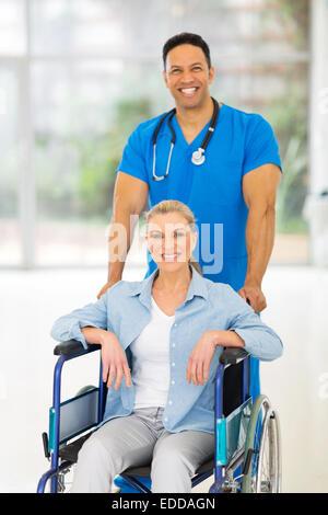 gut aussehend männlichen Krankenschwester kümmert sich um ältere Patienten im Rollstuhl - Stockfoto