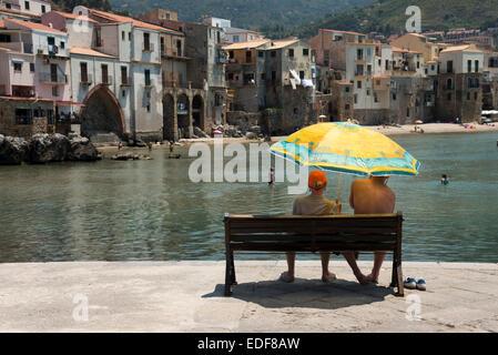 Zwei Menschen sitzen auf einer Bank unter einem Sonnenschirm mit Blick auf den alten Hafen und alten Gebäuden in - Stockfoto