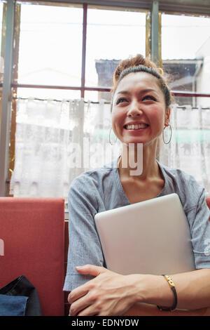 Eine Frau hält einen Laptop in die Arme und drinnen sitzen. - Stockfoto
