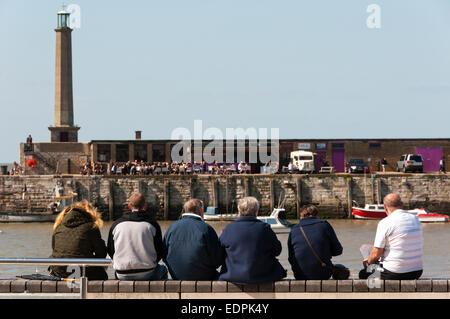Menschen sitzen an Wand in Margate direkt am Meer. - Stockfoto