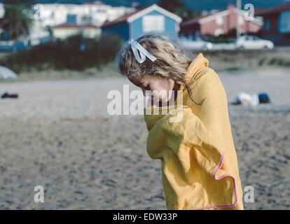 Mädchen mit einem Handtuch am Strand am Ende des Tages Sommer trocknen - Stockfoto