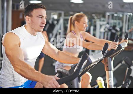 Porträt des jungen Mann und Frau beim Training im Fitness-Studio - Stockfoto