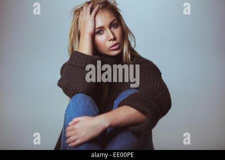 Studioaufnahme von attraktiven jungen Frau tragen Pullover mit der Hand im Haar. Schöne weibliche Modell Blick in - Stockfoto