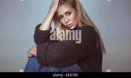 Porträt der schönen blonden Frau in Pullover Blick in die Kamera. Hübsche junge Frau im Studio. - Stockfoto