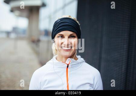Porträt von fröhlichen jungen Fitness-Frau. Lächelnde junge Sportlerin in Sportbekleidung im Freien. - Stockfoto