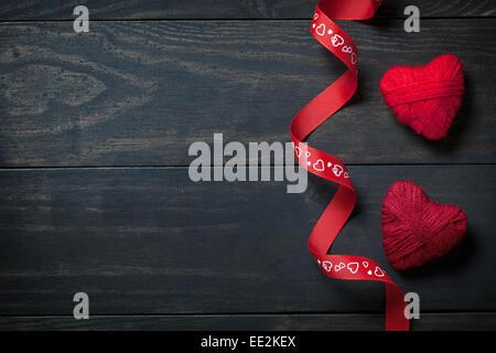 Rote Herzen aus der Wolle auf hölzernen Hintergrund zum Valentinstag. Kopieren Sie Raum. Ansicht von oben - Stockfoto