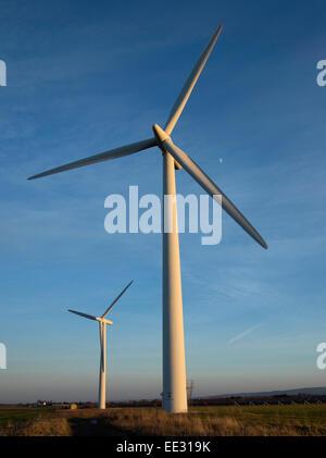 Zwei Windkraftanlagen, gegen einen blauen Himmel und der Mond an einem Wintertag in der Westmill Windfarm kooperative - Stockfoto