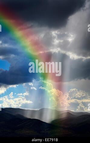Sonnenlicht Strahlen aus den Wolken fallen auf dunkle Gebirgskette mit Regenbogen - Stockfoto