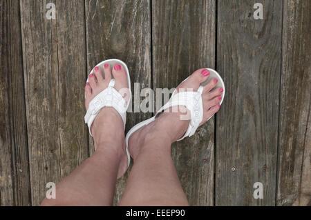 Füße auf unfertige Holzoberfläche in Sandalen - Stockfoto