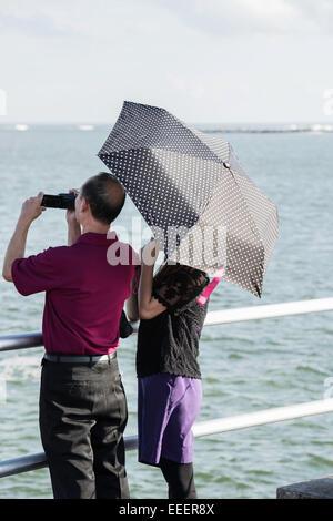 Rückansicht des älteren asiatischen Mann mit Camcorder und Frau unter einem Polk versteckte-a-dot Dach stehend an - Stockfoto