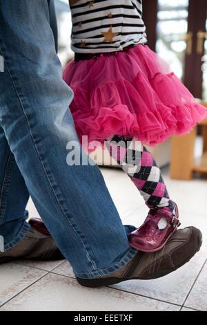 Kleine Mädchen auf ihren Vater stehen die Füße tanzen. - Stockfoto