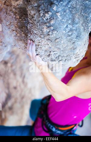 Ansicht der jungen Frau, die natürlichen Felsen klettern beschnitten, die hand im Fokus - Stockfoto