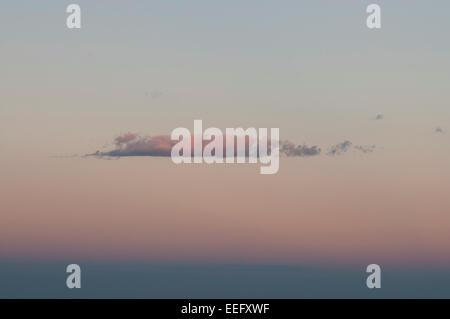 Vereinzelte Wolken gegen orangefarbenen Himmel bei Sonnenuntergang - Stockfoto