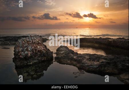 Sonnenuntergang über dem Meer und die felsige Küste mit antiken Ruinen in Mahdia, Tunesien - Stockfoto