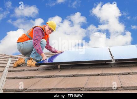 erfahrene Arbeiter überprüfen Sonnenkollektoren auf dem Hausdach - Stockfoto