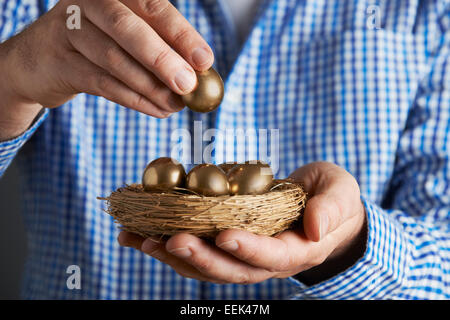 Mann hält Nest voller goldenen Eiern - Stockfoto